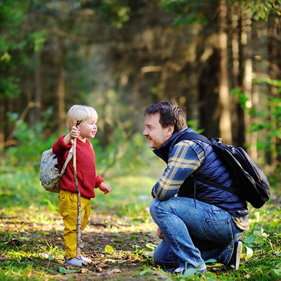Dad with son in the woods to represent families