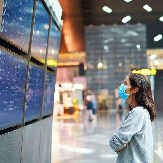 Woman in virus protection face mask looking at information board checking her flight in international airport.